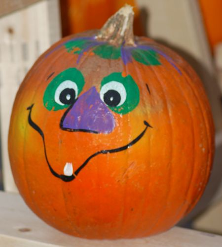 painted pumpkin face photos   goofy-faced pumpkin painted with Halloween witch colors.