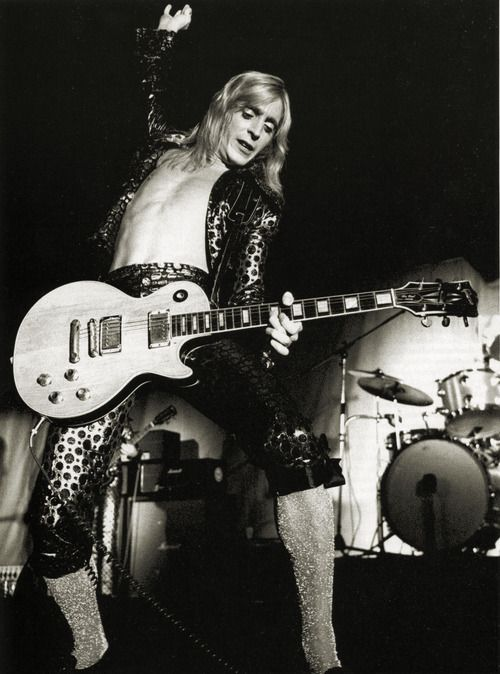 """Mick Ronson on stage.Michael """"Mick"""" Ronson foi um guitarrista, compositor, arranjador e produtor musical inglês. É conhecido por seu trabalho com David Bowie, como um dos Spiders from Mars. Wikipédia Nascimento: 26 de maio de 1946, Kingston upon Hull, Reino Unido Falecimento: 29 de abril de 1993, Londres, Reino Unido Grupo musical: Mott the Hoople (1974) Filme: Ziggy Stardust and the Spiders from Mars"""
