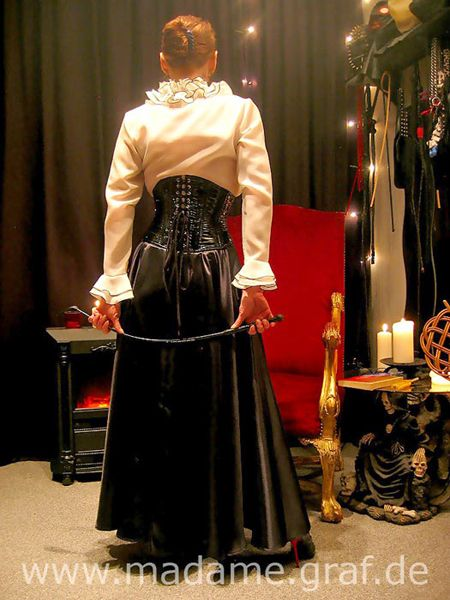 Gouvernante, Lackkorsett, Lederrock, Highheels, Nylons, Satinbluse, strenge Frisur und Gerte - alles da… Governess, Vinyl corset, leather skirt, high heels, nylons, satin blouse, strict hairstyle and crop - all here.