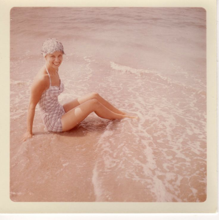 Smiling sixties girl wearing a one-piece plaid swimsuit dips her toes in the ocean.
