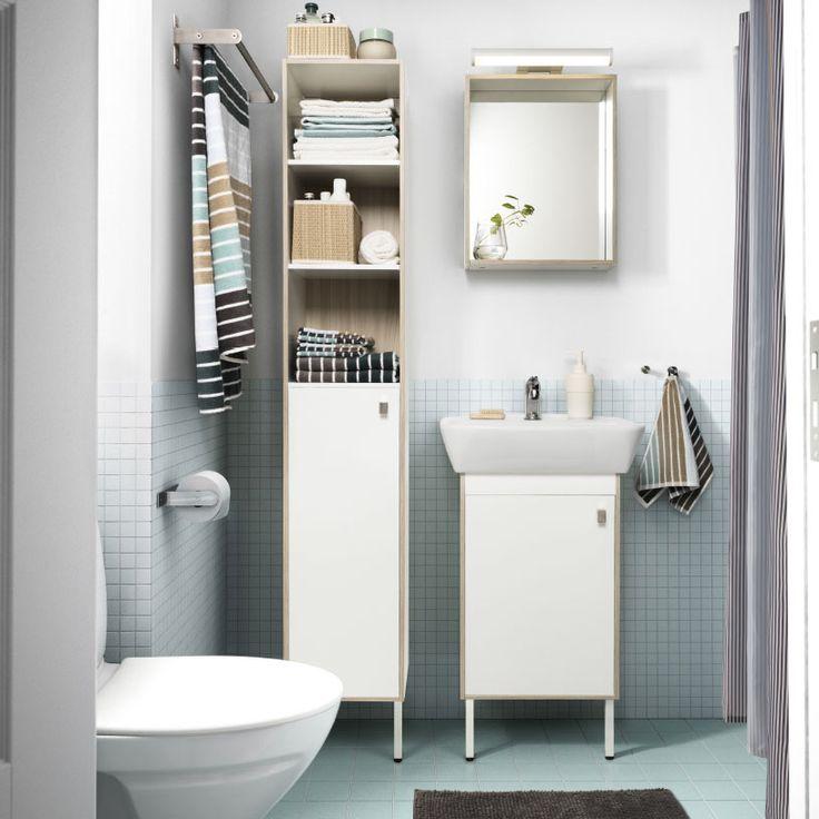 Un baño pequeño con azulejos azul claro en el suelo, un armario alto blanco, un espejo y un armario de lavabo. Acabado con toallas rayadas en azul claro, marrón y blanco.