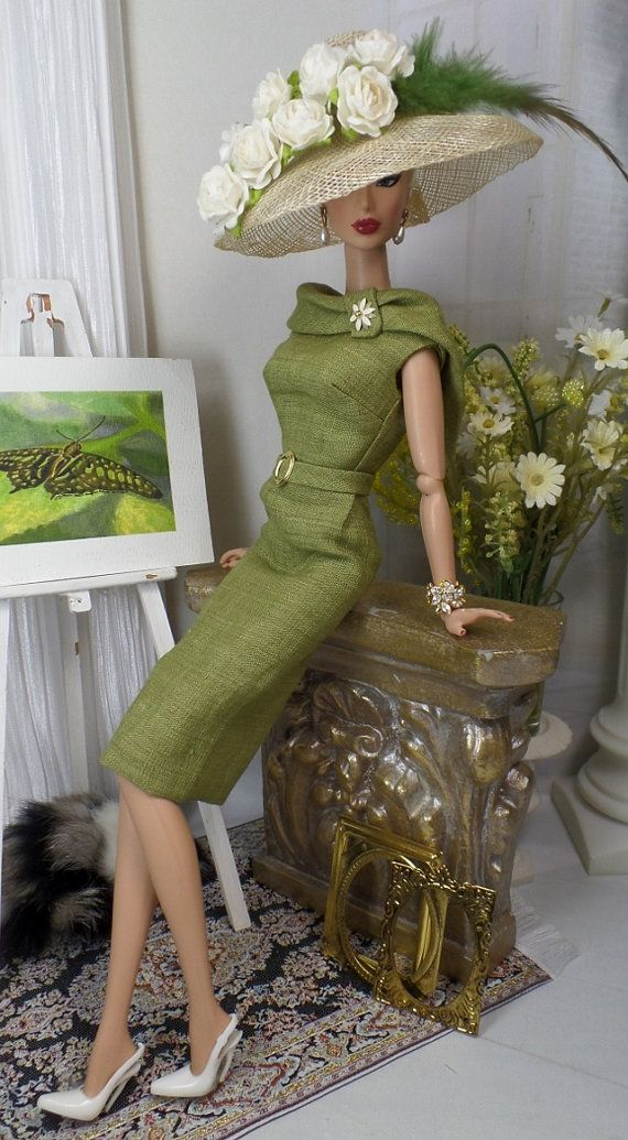 A classic sheath cut from olive handkerchief linen, fully lined in china silk, and features a portrait collar bodice with tab, two tone daisy brooch, attached belt with gold-tone buckle and button over snap back closure. Natural Sinamay hat decorated to match