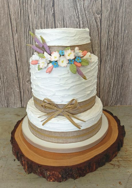 "A perfect cake for a country house or barn wedding.  The cake is coated in royal icing, textured to give a rustic, informal look.  Each tier is wrapped in a hessian ribbon, topped with a raffia band. The pretty design is finished with a raffia and cord bow to the middle tier and a sweet little spray of hand made sugar flowers, featuring lavender and apple blossom.  As seen : 6"", 8"" and 10"" tiers."