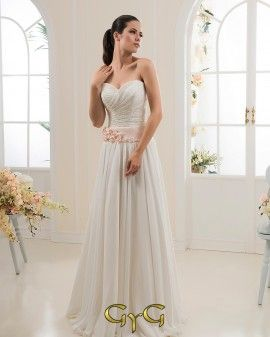 El vestido de novia Liliana se presenta con un aire romántico y delicado perfecto para las bodas que se realizan en grandes jardines o paradisíacas playas. El vestido lleva un bellísimo escote con forma de corazón y un fino encaje drapeado que cubre todo el corset del vestido y que ayuda a realzar el busto. Para separar el corset de la falda el vestido luce un amplio y origínal cinturón de satén color rosa con pequeñas flores y delicada pedrería.