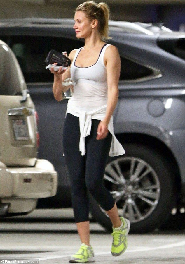 Breaking a sweat: The 42-year-old actress has remained dedicated in her four-day-a-week workouts and her long-time trainer (pictured in May 2014 leaving a gym in Los Angeles)