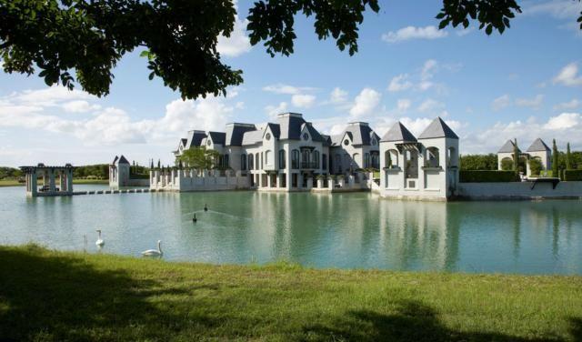 Un gran castillo moderno rodeado de un lago con cisnes