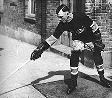 Photo noir et blanc de Joe Hall en tenue de hockeyeur à l'extérieur d'un bâtiment. Mort de la grippe espagnole en 1919.