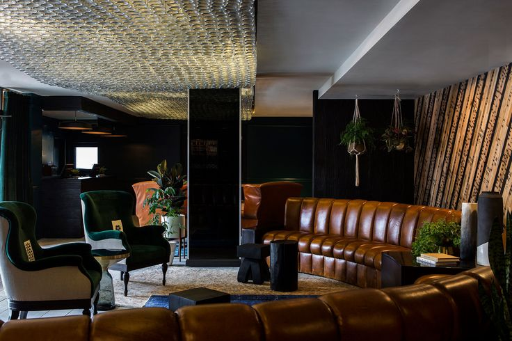 A curvaceous leather banquette sits opposite two velvet wing chairs in the lobby, and beneath a custom lighting installation that was designed by Hollis and made with 3,100 recycled whiskey bottles. | The Buchanan Hotel in SF