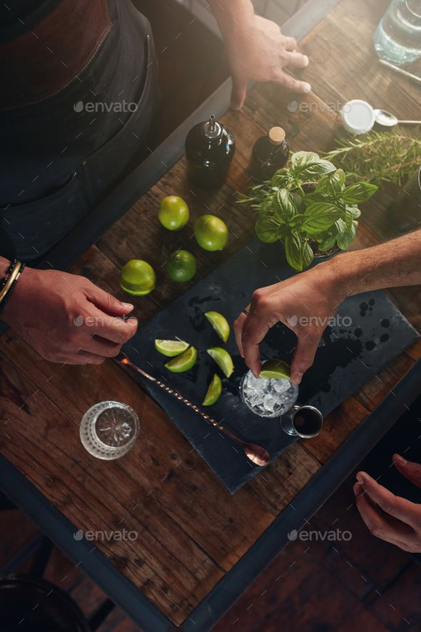Barmen preparing refreshing new cocktail by jacoblund. Closeup of hands of barman squeezing the lemon into the glass. Two barmen preparing refreshing new cocktail at the co...