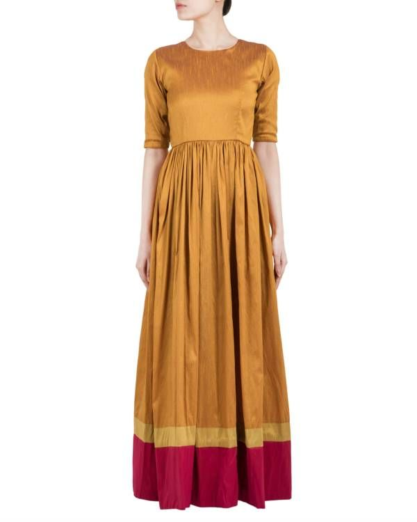 Gold brown and red double border dress    Raw silk gold brown maxi dress with green and red border at bottom. The dress is fitted under bust, has gathers at waist, with a straight but slightly flared fall. It has side pockets and zip at back for closure. The bodice has santoon fabric lining.