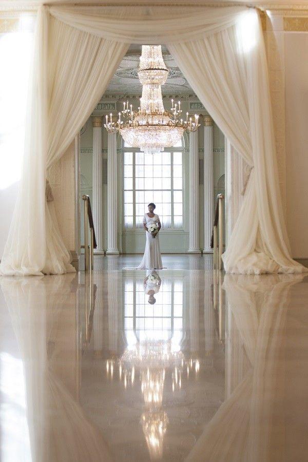 Bride standing in elegant modern wedding venue @myweddingdotcom
