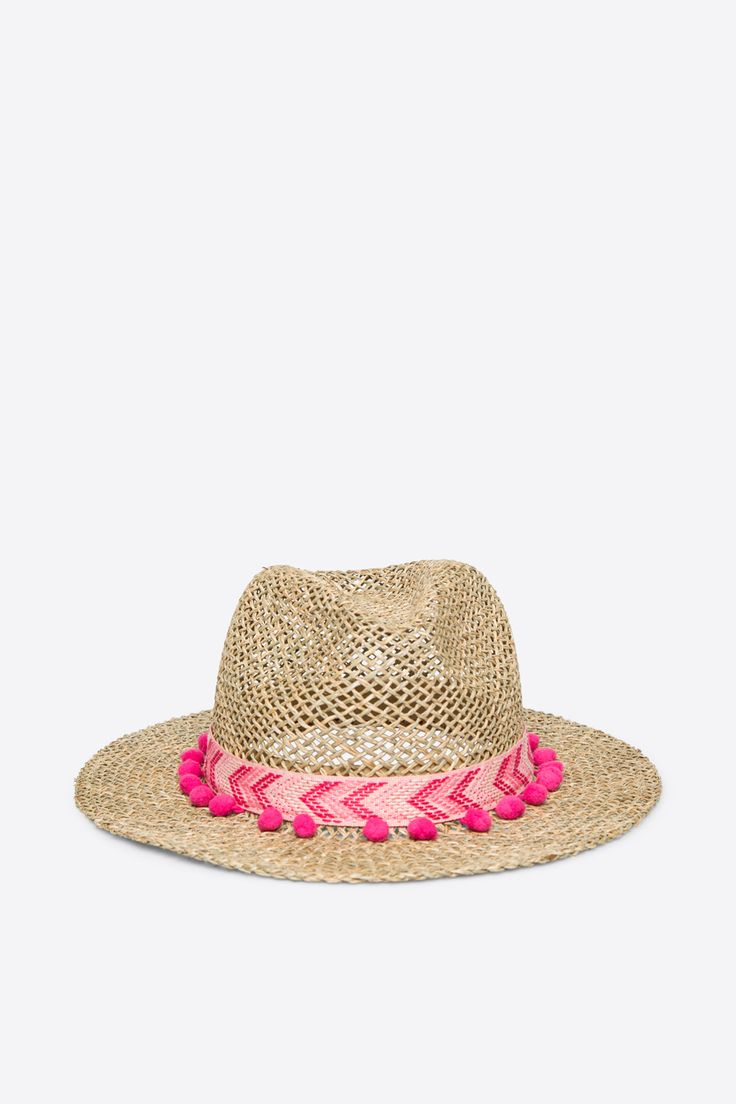 Straw sun hat adorned with pompoms.