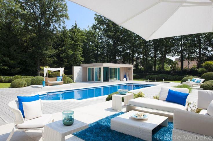 Diepblauw keramisch zwembad omringd door exclusief tuinmeubilair,   De Mooiste Zwembaden