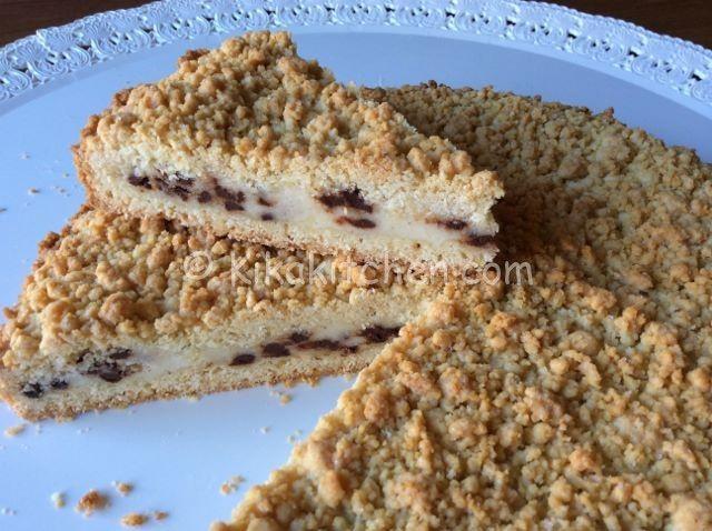 La sbriciolata ricotta e cioccolato è un dolce con frolla sbriciolata. La superficie croccante contrasta con il morbido ripieno di ricotta e cioccolato.