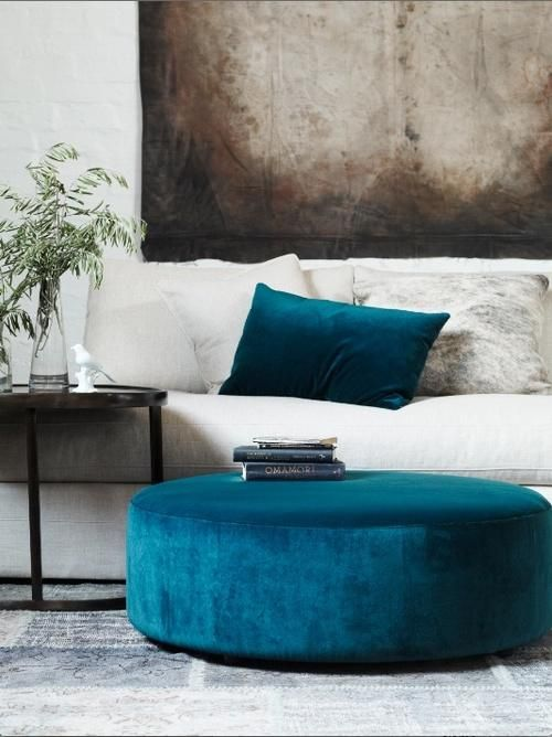 I love the teal velvet contrasting with the white sofa and then the rustic, almost industrial feeling art piece. Perfection.