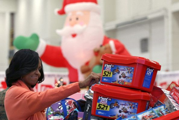 Michelle Obama Photos - First lady Michelle Obama helps sort toys and gifts during an event at Joint Base Anacostia-Bolling on December 11, 2012 in Washiington, DC. The toys were donated by the staff members of the Executive Office of the President to the Marine Corps' Toys for Tots Campaign. - Michelle Obama Photos - 3976 of 9409