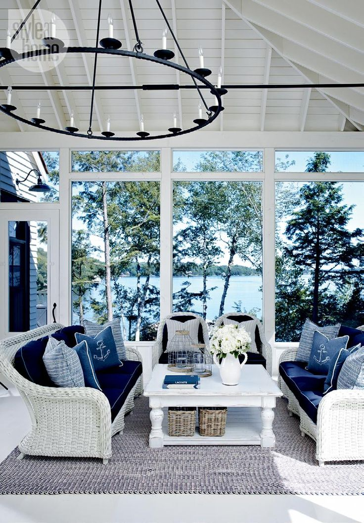 "The Muskoka room—White wicker furniture with nautical-themed toss cushions keeps the feeling as fresh as the air in the Muskoka room. ""We entertain all summer and enjoy spending lots of time in here,"" says homeowner Kai tukums. ""It's an extension of the house."""