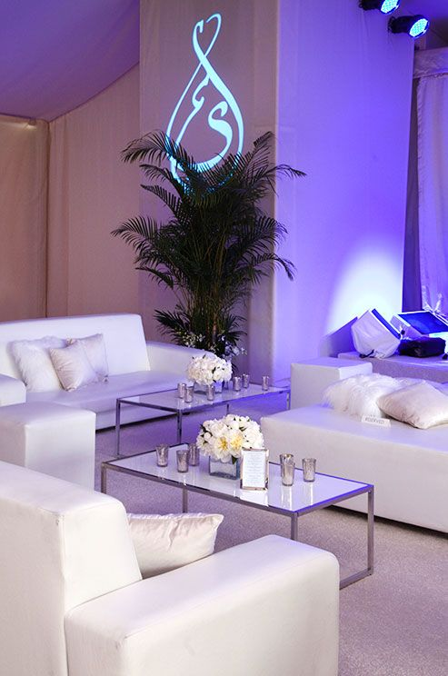 White fur and light pink pillows atop plush white couches create an airy, romantic lounge.