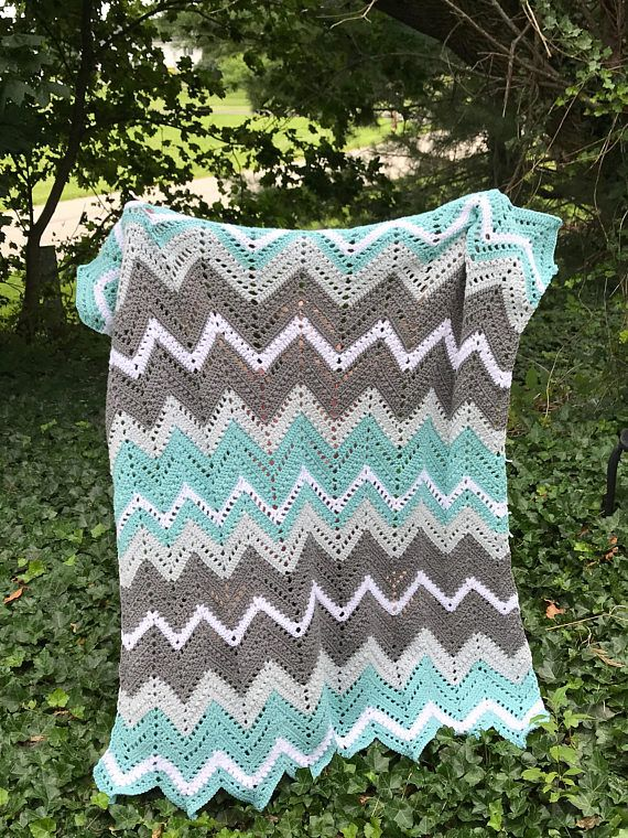 A handmade crochet chevron afghan in paper white, slate grey, stormy grey, and washed teal. Made with super soft acrylic Aran yarn by an Army veteran, just for you! This blanket is made to Order and can take up to 8 weeks to ship (unless otherwise notified). BLANKET TYPE: Lapghan