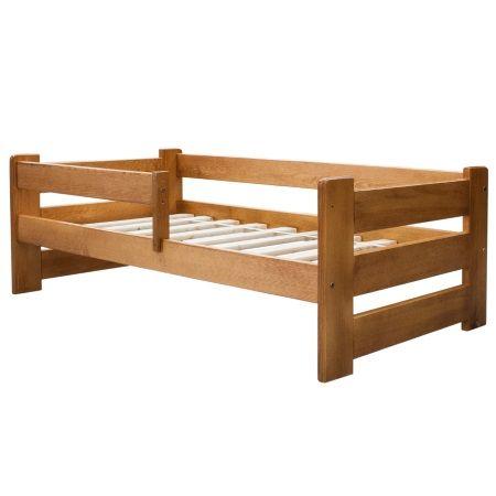 Klasyczne drewniane łóżko dziecięce z barierką, wykonane z litego drewna sosnowego w kolorze olchowym.