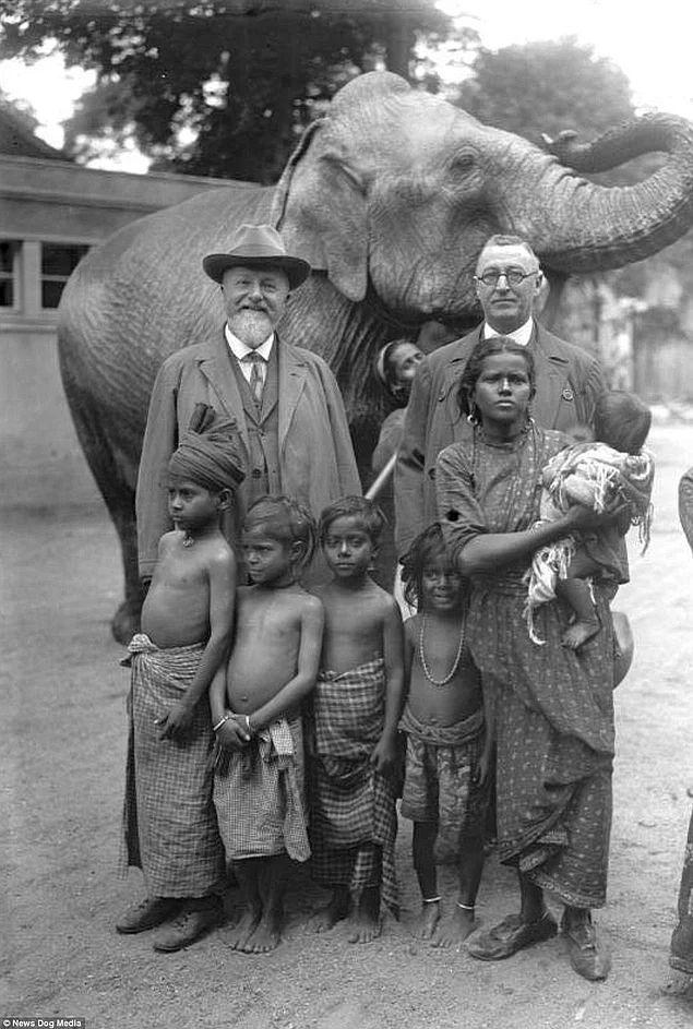 Alman zoolog Prof. Lutz Heck (solda), 1931 yılında Afrika'ya getirilmiş bir fil ve Afrikalı aile ile poz veriyor.