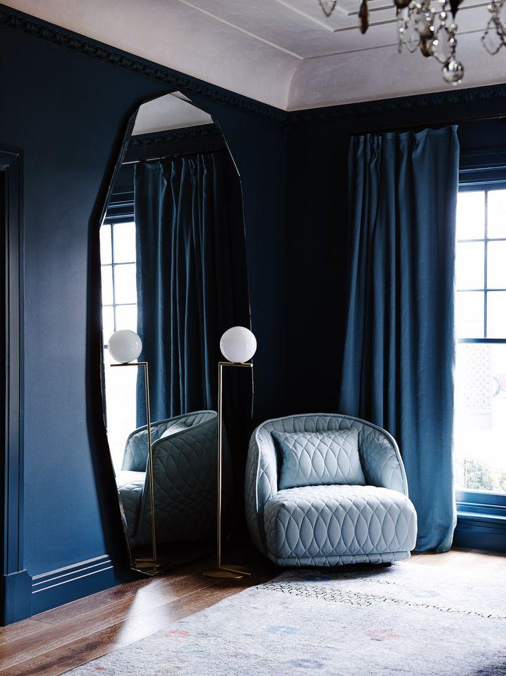 Dark blue room with an elegant interior design: we love the light blue velvet armchair and the big mirror.