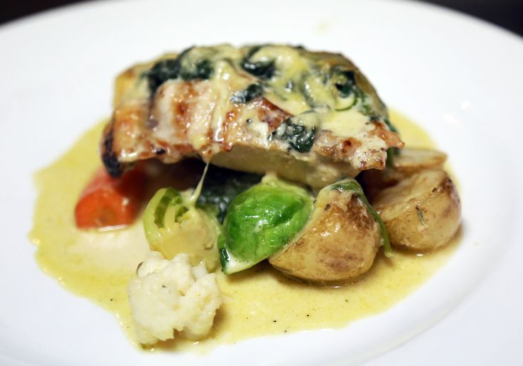 Pear Tree Cafe's Oven Baked Boneless Chicken leg filled with Brie, Pesto & a White Wine Creamy Sauce.