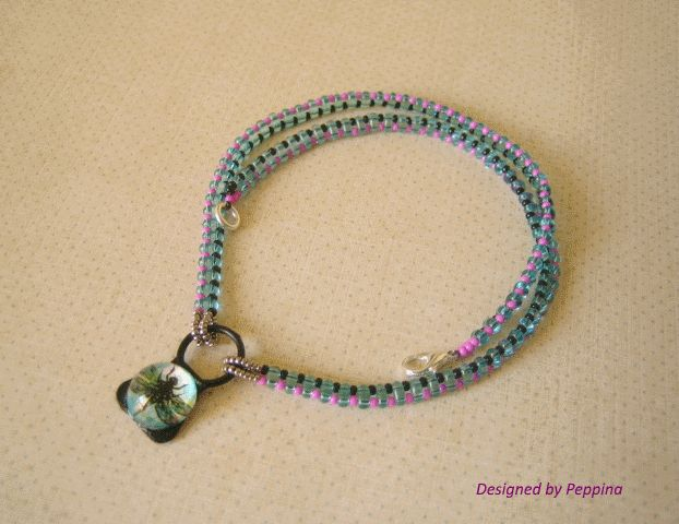 Mixed media (glass cabochon, pmc base, rubber ring, beads.