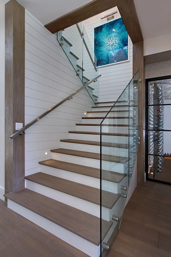 Staircase. Glass stair. This stunning staircase was designed by the architect and builder. The staircase features glass stair rail with steel hand rail and shiplap walls. #stair #glass #staircase Patterson Custom Homes. Interiors by Trish Steele of Churchill Design.