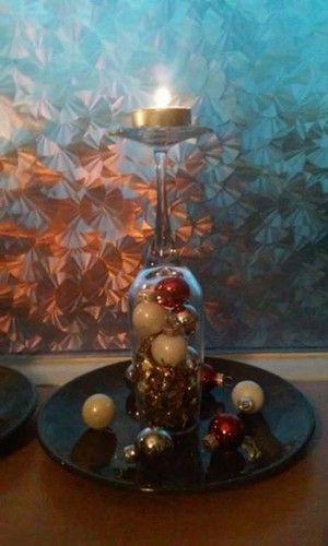 champagneglas waxine houder  men neme: 1 champagneglas lijmpistool kerstballetjes slinger bordje  vul het champagneglas met lijm doe hier in je kerstballetjes doe ook daar lijm op slinger er bij lijm de rand van je glas druk dit tegen een bord decoreer met versieringen