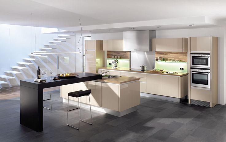 Moderne keuken met kookeiland en keukenkasten in een gebroken witte kleur. Aan het kookeiland is een toog aangemaakt waar ook aan kan gegeten worden.