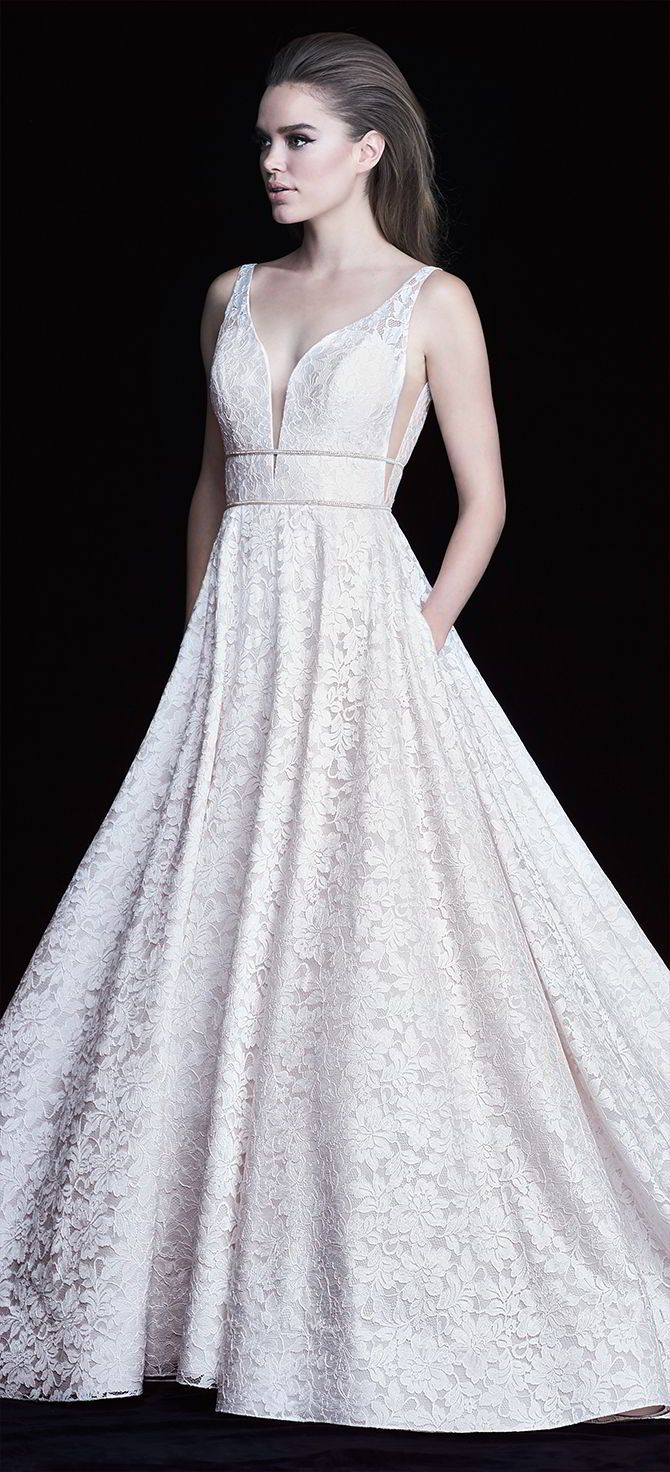 """Paloma Lace Wedding Dress. Paloma Lace gown with plunging neckline bodice with double beaded bands across midriff and waist. V-shaped Italian Tulle inserts at side seams on bodice. Full circle skirt with pockets finished with 4"""" horsehair edging on lace hem."""