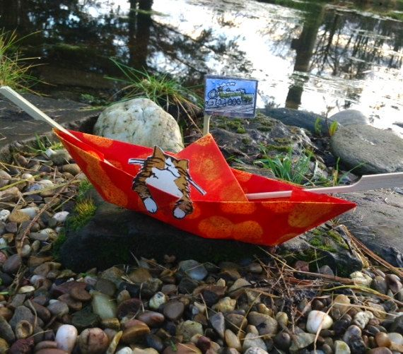 A sweet paper boat in memory of Twitter star @MYSADCAT -also known as The Bear (RIP) sadly departed aged 21 years. The Bear who started life as an abandoned kitten gave joy to many. All proceeds Millwood, a local Cat Rescue in Nottinghamshire. One of several catboats all different, all original, one off and hand made. Hand decorated (dyed batik) paper folded into a traditional paper boat, with hand printed cats and a tiny water colour flag (by Mick Cox).  One only per person please…