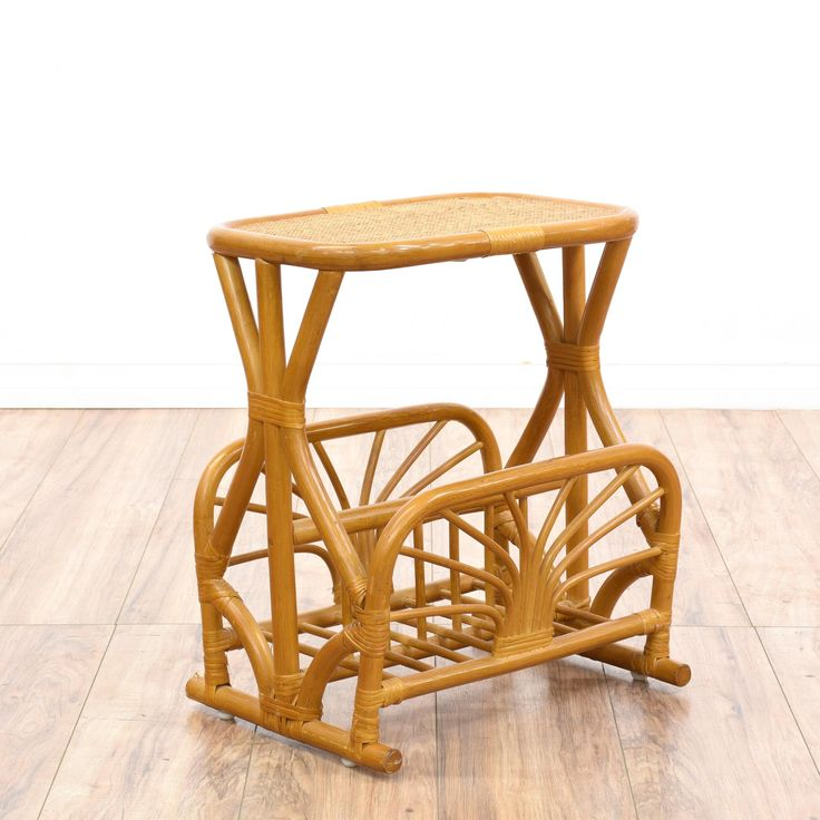 This tropical magazine rack side table is featured in a rattan with a glossy light wood finish. This bohemian end table has a bottom magazine rack with a round wicker table top and curved accents. Perfect for a covered porch or patio! #bohemian #tables #endtable #sandiegovintage #vintagefurniture
