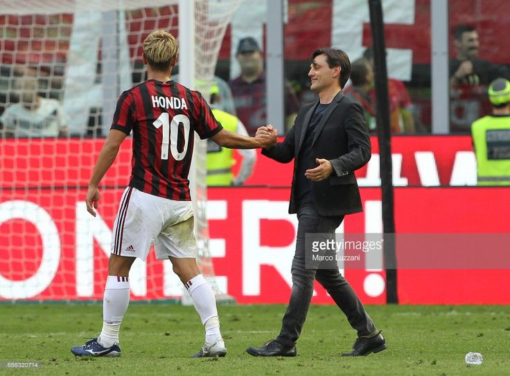AC Milan coach Vincenzo Montella (R) shakes hands with Keisuke Honda (L) at the end of the Serie A match between AC Milan and Bologna FC at Stadio Giuseppe Meazza on May 21, 2017 in Milan, Italy