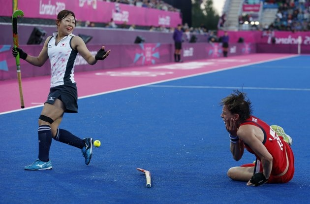 Britain's Kate Walsh (R) falls onto the pitch after getting hit in the face by Japan's Nagisa Hayashi during their women's Group A hockey match at the London 2012 Olympic Games at the Riverbank Arena on the Olympic Park in London July 29, 2012. REUTERS/Suzanne Plunkett (BRITAIN  - Tags: SPORT OLYMPICS SPORT FIELD HOCKEY)