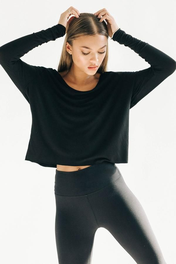 e7c4970f487 Front view of model raising her arms in the flowy scoop neck black Laid  Back Long Sleeve with fitted sleeves