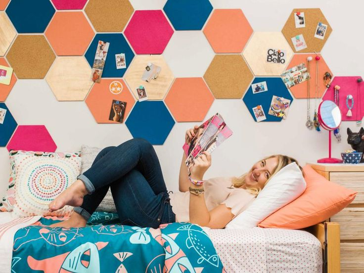 Deck out your dorm room with stylish decor ideas that won't break the rules, like this wall of painted hexagon-shaped cork pieces, attached to the wall with removable adhesive strips.