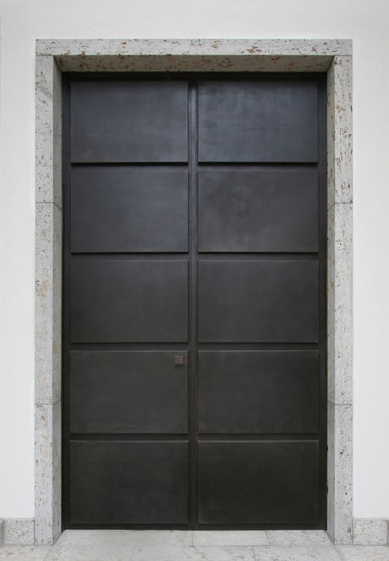 Classically influenced double door in bronze and stone by German architects. Architekt Carsten Vogel