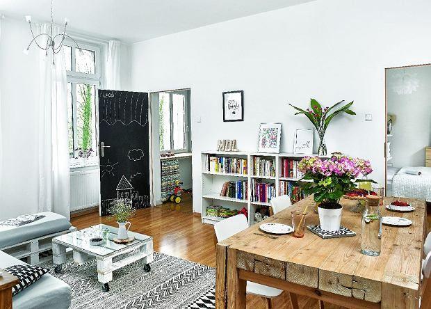 Biel i drewno decydują o wyrazie tego mieszkania. Ciekawostką jest farba tablicowa na drzwiach.