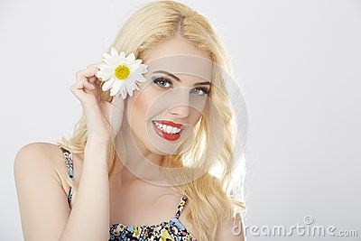 Smiling lady posing with a daisy flower in her blond hair.