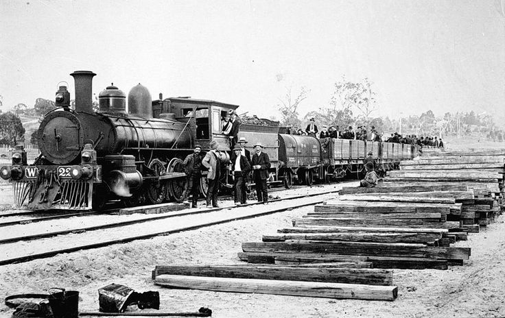 A train load of East Gippsland rail gangers in open trucks with a pile of sleepers in the foreground. The locomotive is a Victorian Railways W class 4-6-0 built by the Baldwin Locomotive Works in the USA. A total of 13 of this class were used in Victoria built between 1879 and 1883 with one example built in Ballarat by the Phoenix Foundry.