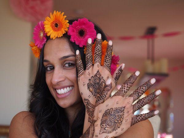 A gorgeous bride wears a colorful flower crown at her mehndi. Henna patterns by www.hennalounge.com #desi #indian #wedding #mehndi #sanfrancisco #flowers #gerbera #daisies