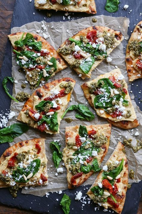 Hummus Flatbread with Sun-Dried Tomatoes, Spinach, and Pesto is an easy appetizer perfect for a healthy snack @sabradips #nationalhummusday #ad #vegetarian