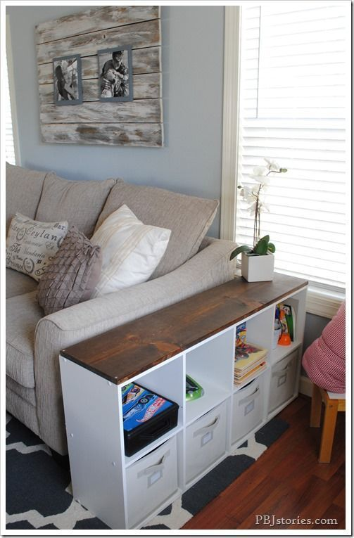 **Coffee Table Cube - she turned an old black bookshelves into a piece that would better fit our living space décor. A quick paint job, and a durable wood top and some fabric bins.