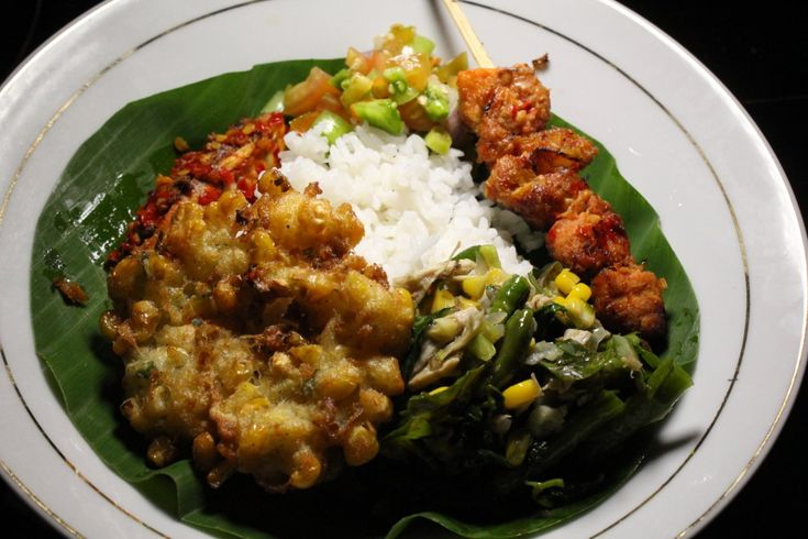 Here's a plate of Nasi Manado. Manado is a city in Indonesia, and a style of cooking. The rice (nasi) is surrounded by a skewer of pork and other incredibly spicy foods.