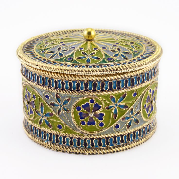 A Norwegian gilded silver and plique-à-jour enamel box, Marius Hammer, circa 1900. Cylindrical, the walls decorated with scattered stylized flowerheads and scrolling gilded filigree on fields of white or pale green between a lappet border of alternating red and blue, the base of the box in gilded silver, the slip-on lid with conforming ornament.