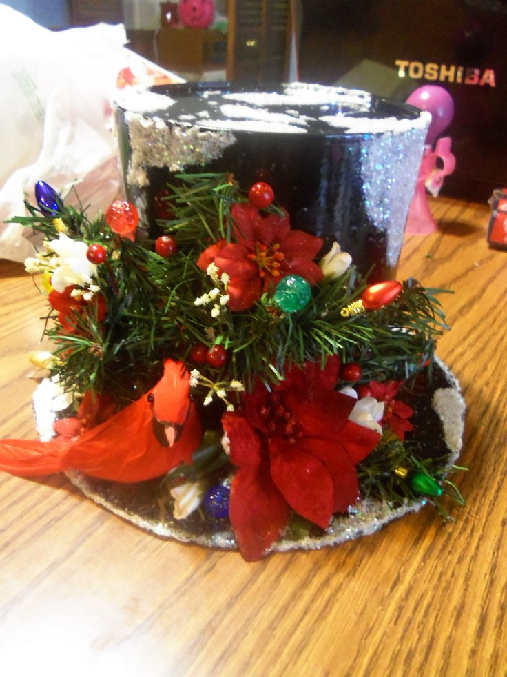 Top Hat / Cookie-Candy Container or Table Decoration. Made with Coffee Can, Cardboard, Black Spray Paint, School Glue/Glitter, for snow, fake Christmas tree stems, Decorations, fake flowers, and use glue gun to glue items on brim of hat.