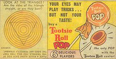 (A vintage Tootsie Roll Pops advertisement.) Tootsie Pops were invented in 1930 by Lukas R. Weisgram, an employee of The Sweets Company of America.  The company changed its name to Tootsie Roll Industries in 1969.