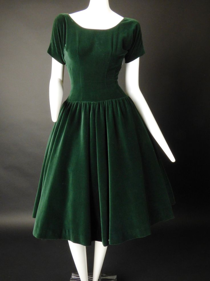 Gorgeous dinner dress in a dark green velvet. The dress has a scoop neckline and is dart fitted at the bust. Short sleeves are cut in one with the bodice. Dart fitted through the midriff and waist to